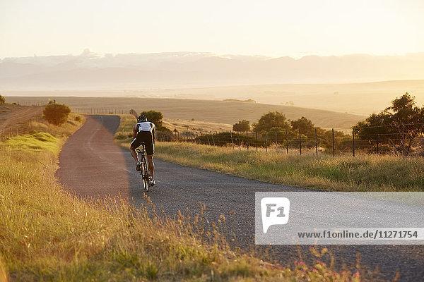 Männlicher Triathlet Radfahrer auf sonniger Landstraße bei Sonnenaufgang