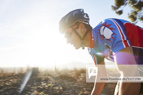 Männlicher Triathlet Radfahrer bei Sonnenaufgang