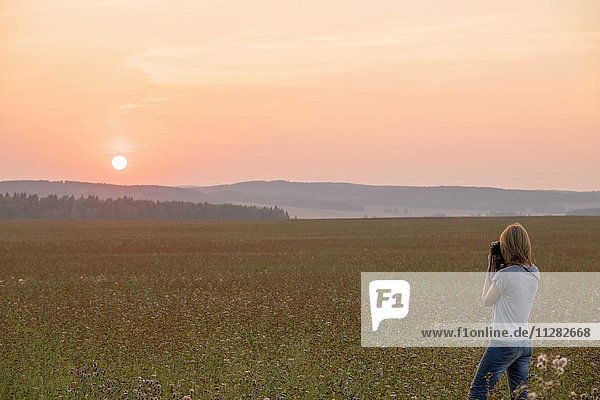 Caucasian woman photographing sunset in field