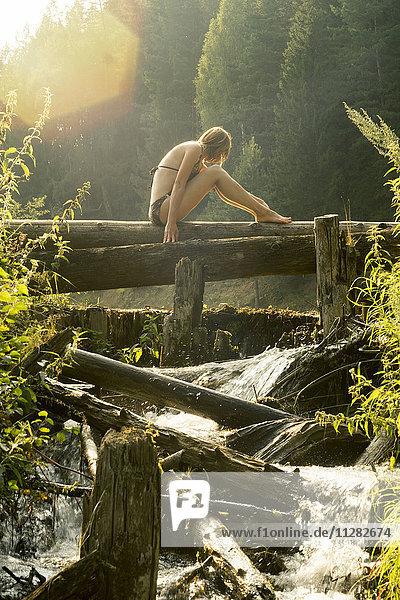 Caucasian woman sitting on log over waterfalls
