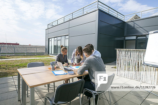 Group of business people working on rooftop terrace