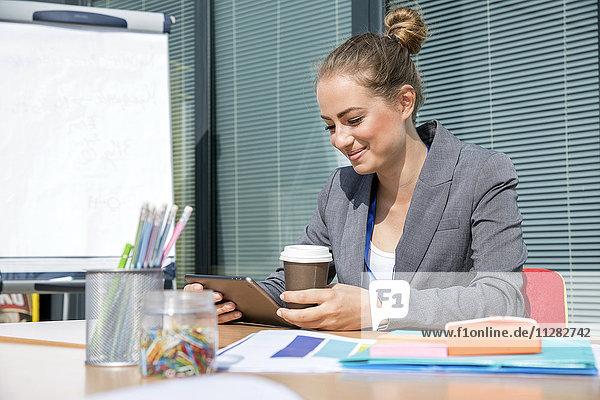 Businesswoman receiving good news on digital tablet