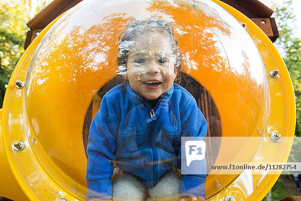 Caucasian baby girl smiling in playground bubble