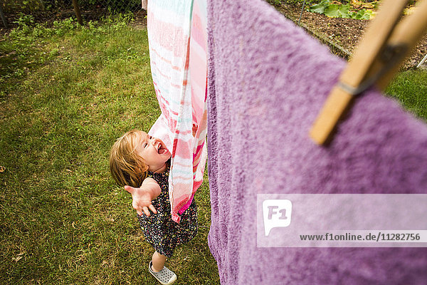Caucasian baby girl playing with towels on clothesline