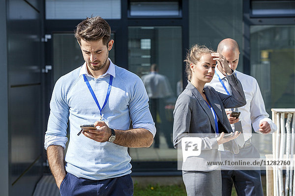 Business people using smartphones outdoors