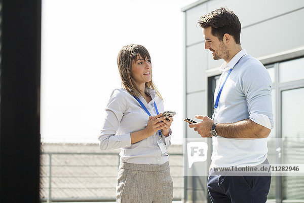 Business couple with smartphones talking outdoors