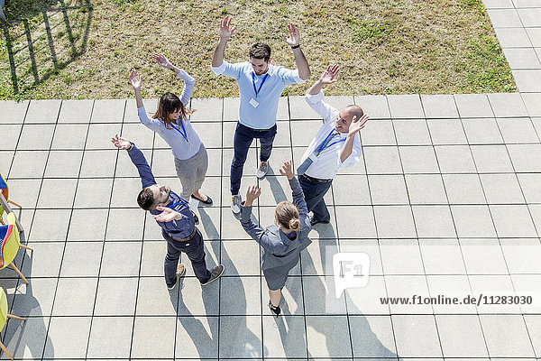 Group of business people raising hands together in a circle