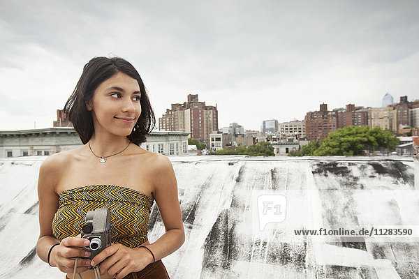 Mixed Race woman on rooftop holding video camera