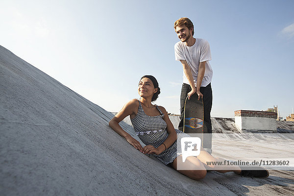 Mixed Race couple on rooftop with skateboard