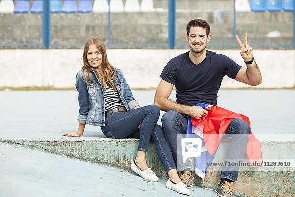 Young couple with French flag making peace sign
