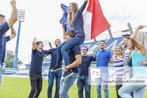 Group of soccer fans celebrating on soccer field