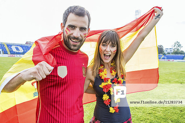 Young couple with face paint waving Spanish flag