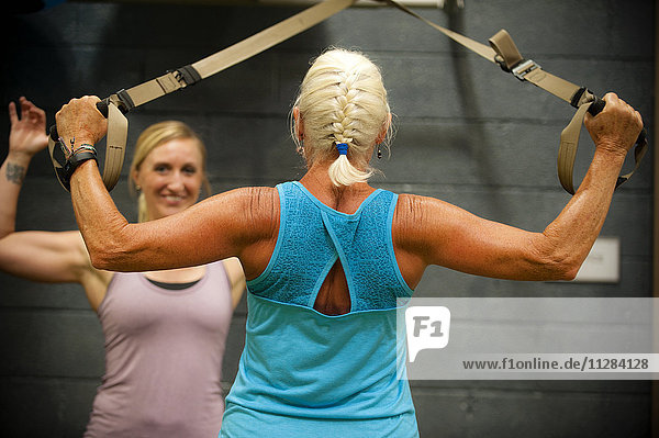 Trainer assisting older woman working out in gymnasium