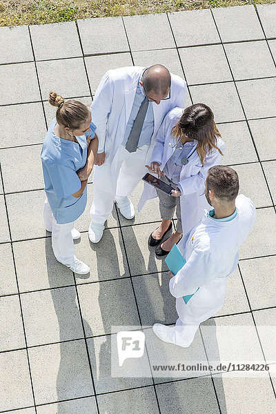 Doctors stand in circle looking at digital tablet