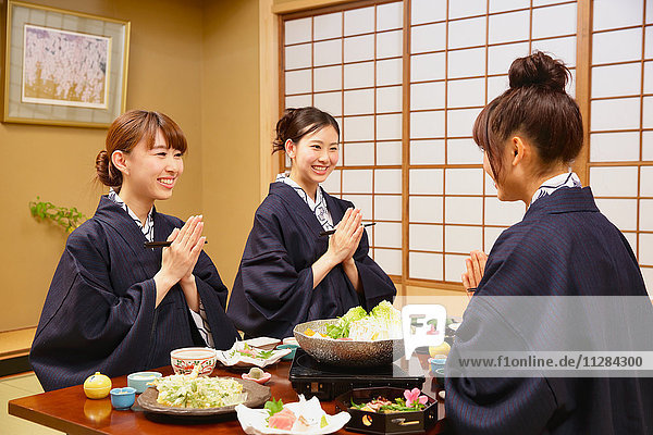 Young Japanese women wearing yukata eating at traditional ryokan inn