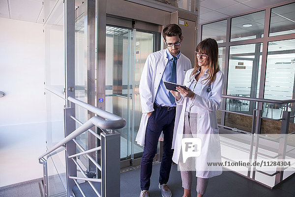 Female doctor and colleague looking at digital tablet