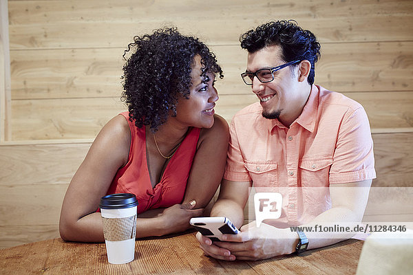Smiling couple using cell phone in coffee shop