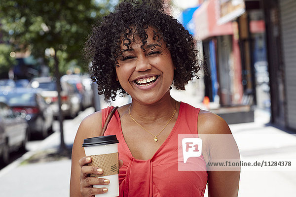 Smiling woman carrying coffee on city sidewalk