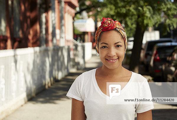 Portrait of smiling Black woman wearing headscarf on city sidewalk