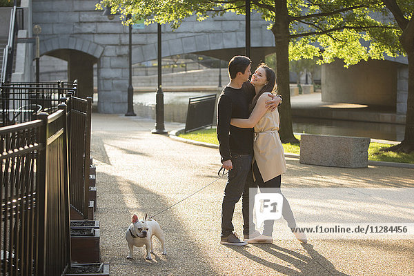 Caucasian couple with dog hugging in park