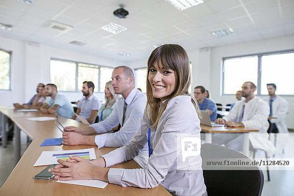 Smiling woman in front of audience in training class