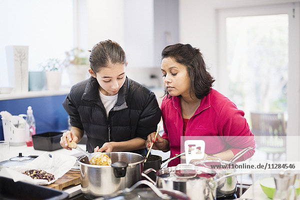 Mother and daughter looking down at cooking food