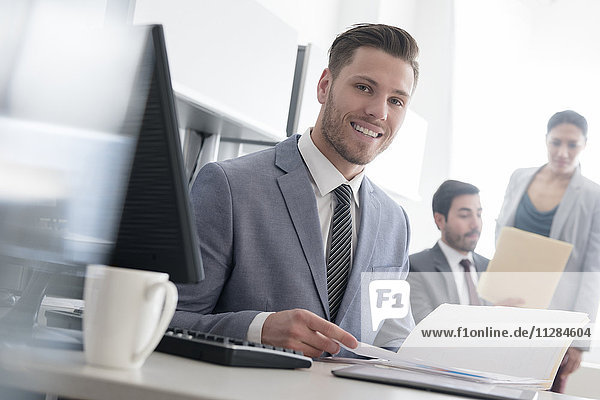 Smiling businessman reading file in office