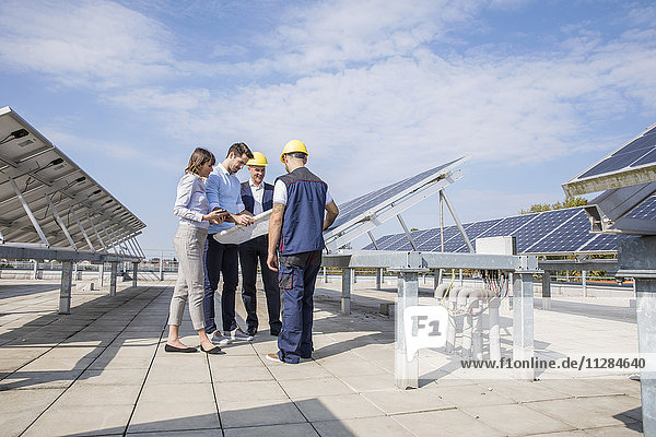 Architects and construction workers inspecting solar power station