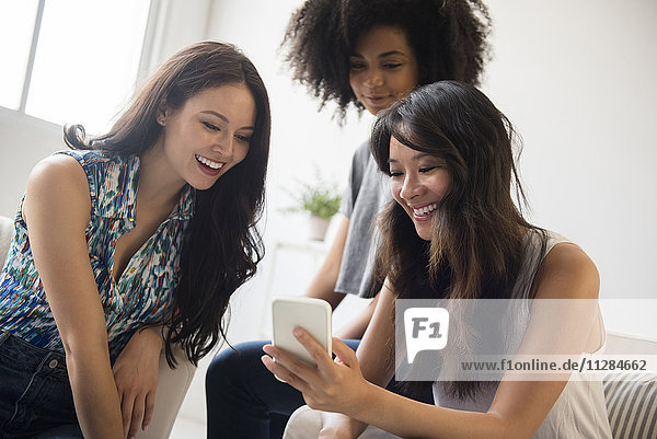 Smiling women texting on cell phone in livingroom