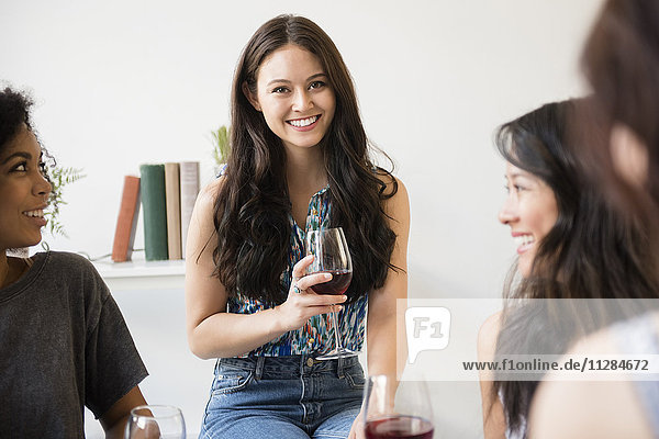 Portrait of smiling woman drinking wine at party