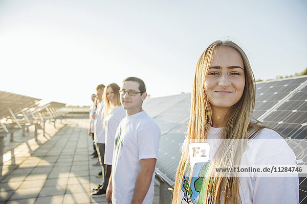 Group of teenage environmentalists in front of solar panels