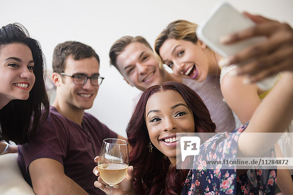 Smiling friends posing for cell phone selfie