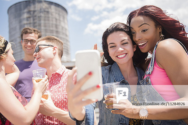Smiling friends posing for cell phone selfie outdoors