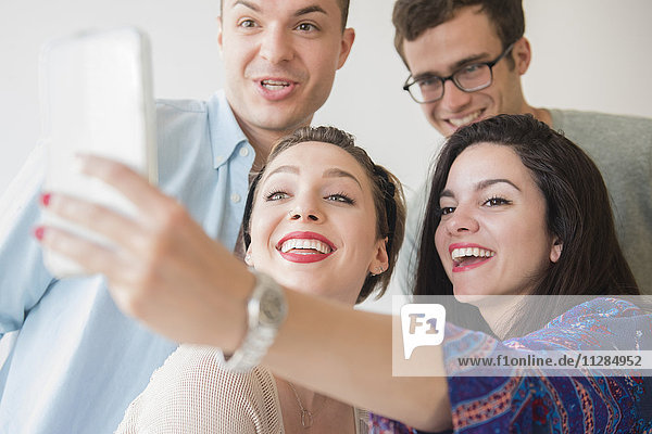 Smiling Caucasian friends posing for cell phone selfie