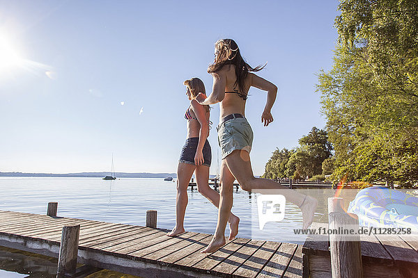 Two young women running on pier by lake