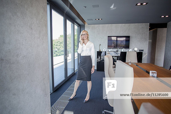 Businesswoman in board room using phone