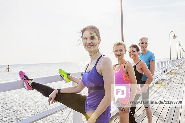 Group of young women on jetty stretching legs