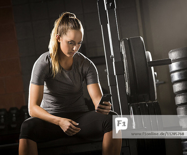 Caucasian woman texting on cell phone in gymnasium