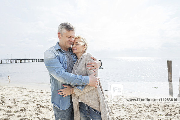 Man on beach embracing girlfriend