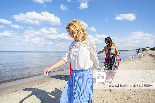 Group of women take a walk along the beach