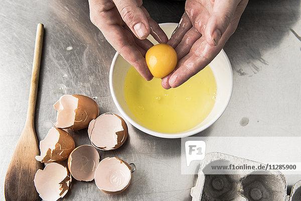 Hands holding egg yolk