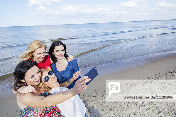 Women on beach taking a selfie