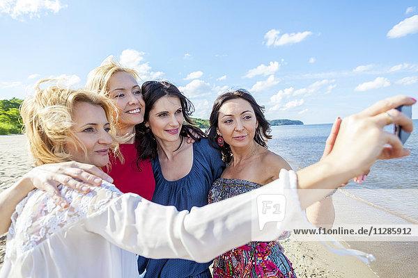 Women on beach taking a selfie