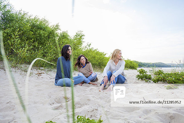 Group of women sitting on sandy beach