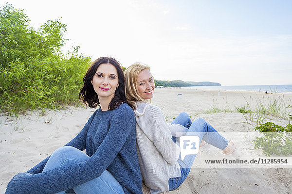 Two women on sandy beach sitting back to back