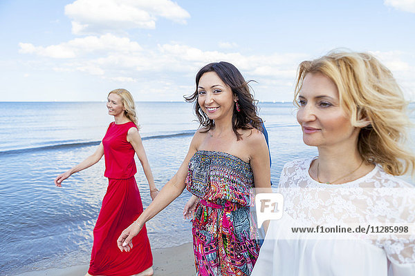 Group of women take a walk along the beach