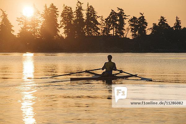 Caucasian man rowing at sunset