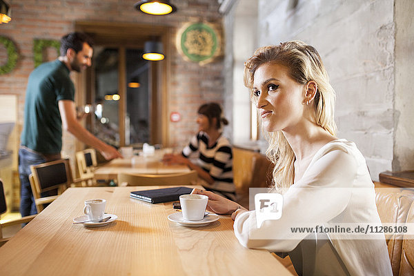 Woman with blond hair drinking espresso in coffee shop