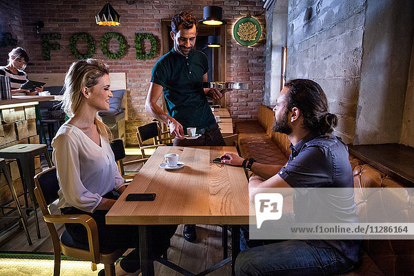 Waiter serving espresso to couple in coffee shop
