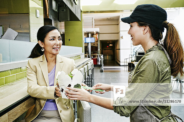 Worker bringing carton of food to businesswoman in food court